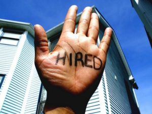 a temporary employee whose hand has the word hired written on it.