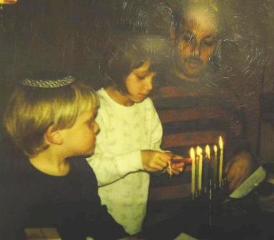 A young Sheliya (C)  lights the Menorah for the first  time, while her little brother, Elan (L), and her father, Doron (R), watch.