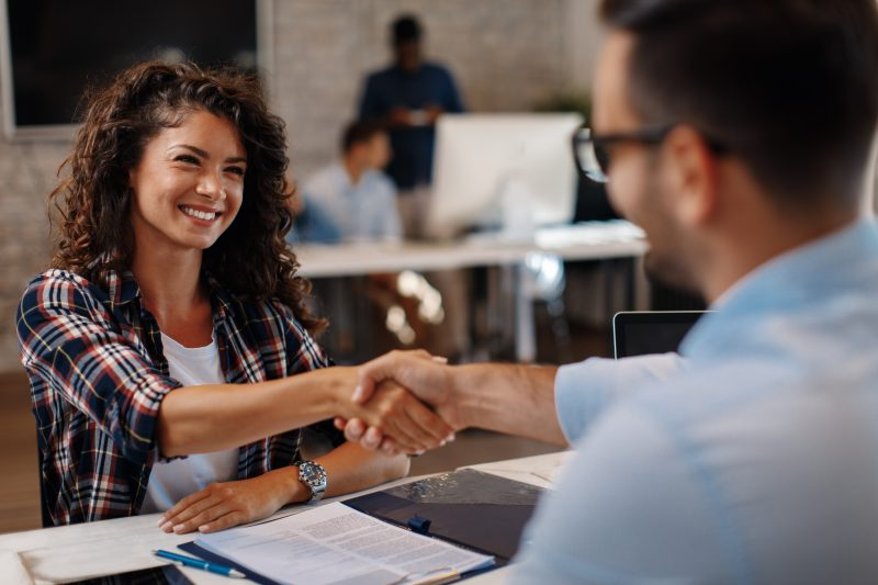 Young woman shaking hands with recruiter after a successful staffing agency interview.