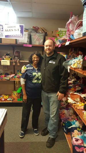 Martha Davis (L), who has voluntarily run Toy Rescue Mission for 20 years, and the owner of Dickey's Barbecue Pit (R) showing some Seahawks and holiday spirit.