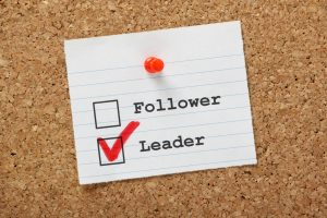 A note with the words leader and follower is pinned to a board. The word leader is checked off.