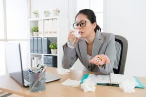 Sick employee blowing her nose at her desk during cold and flu season