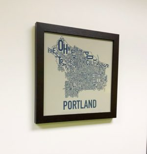 Photo of framed Portland word cloud, hanging in the new Beaverton office