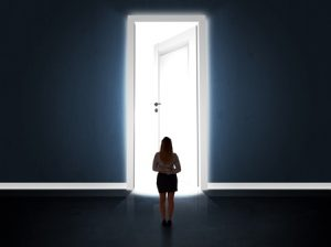 Image of woman standing in front of door, nervous about returning to work after an illness.