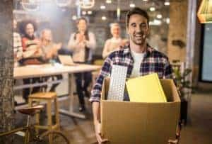 man smiling with a cardboard box full of office supplies