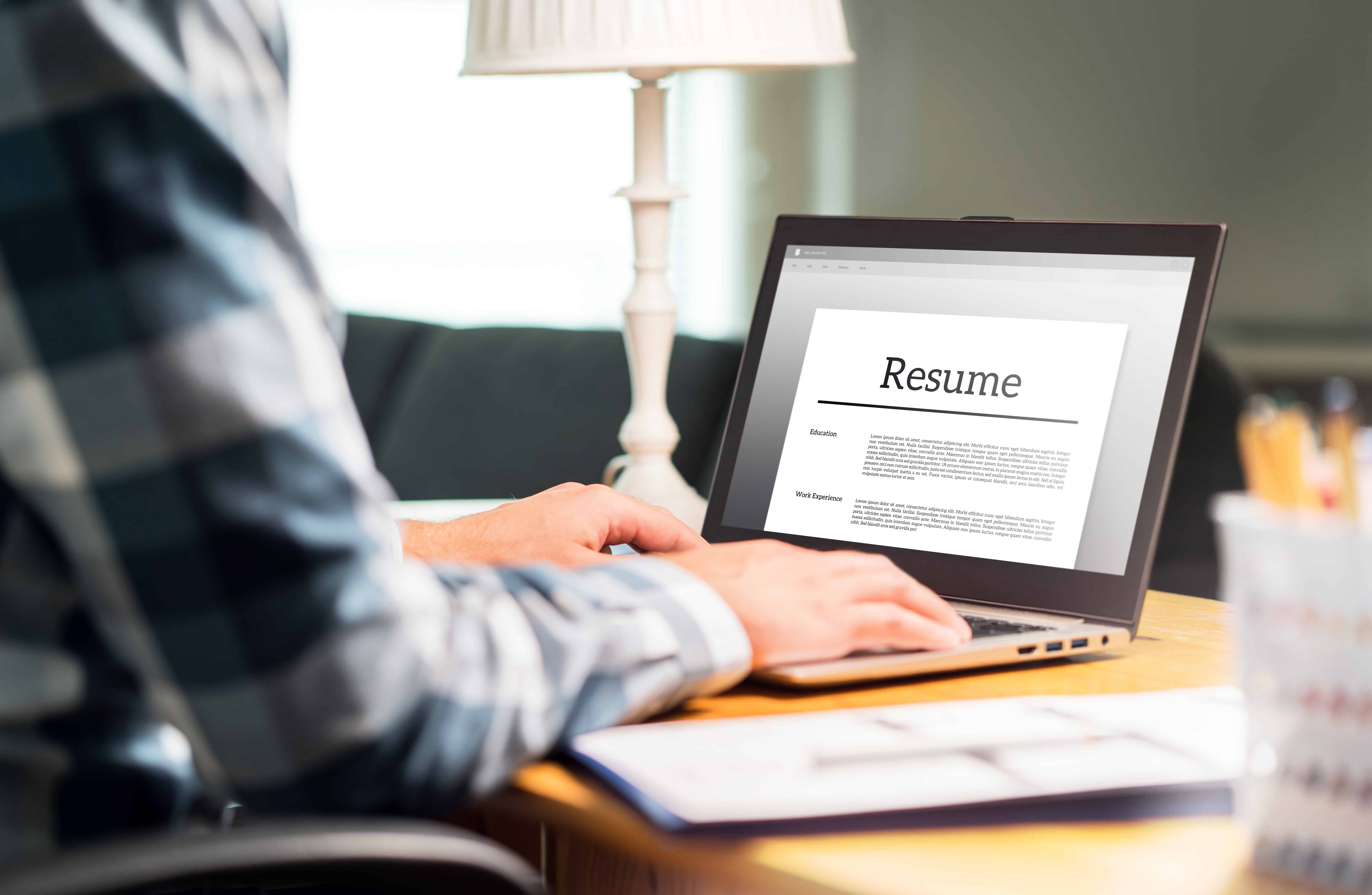 Person writing resume at home on a laptop