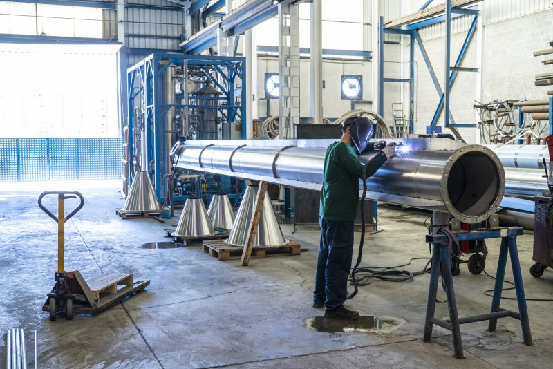 Man in manufacturing welding a pipe