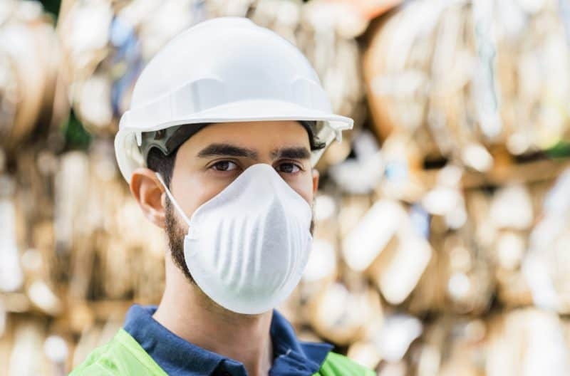 Male worker in mask at recycling center