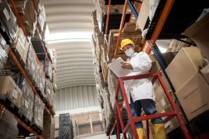 warehouse worker wearing a face mask and social distancing
