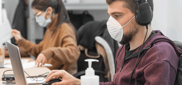 workers on computers with face masks on