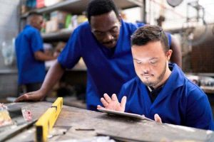 Man with a learning disability using an ipad under manager's supervision
