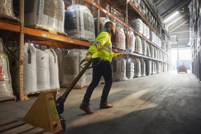 A lone warehouse worker pulls a stacker trolley behind him.