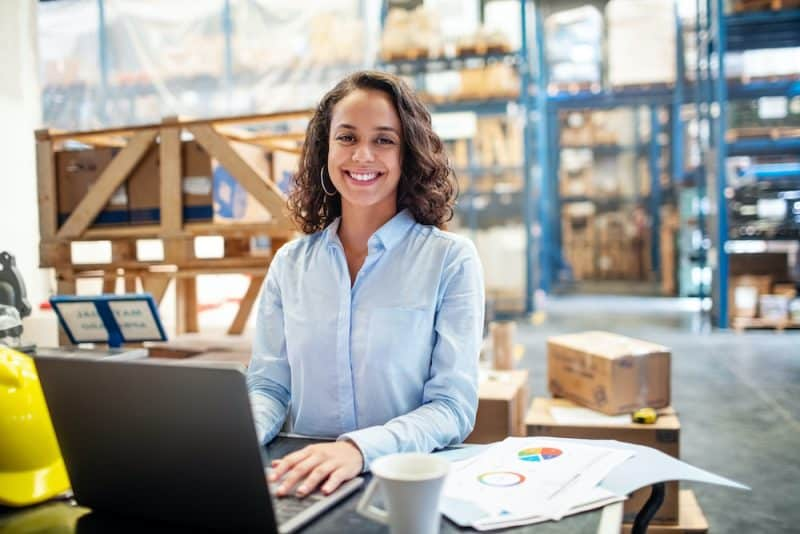 woman using laptop in a warehouse