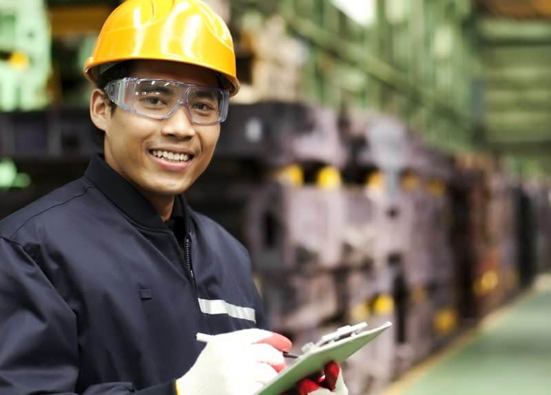 image of worker in manufacturing management role holding clip board