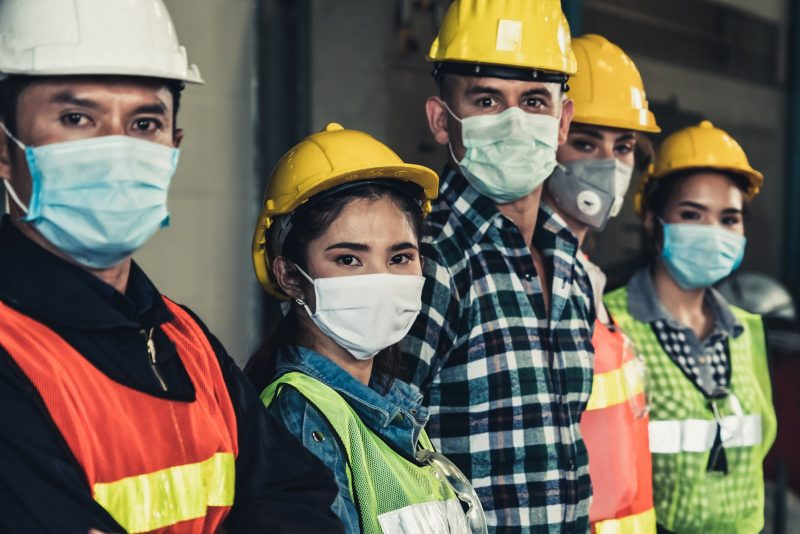 Diverse group of warehouse workers in masks