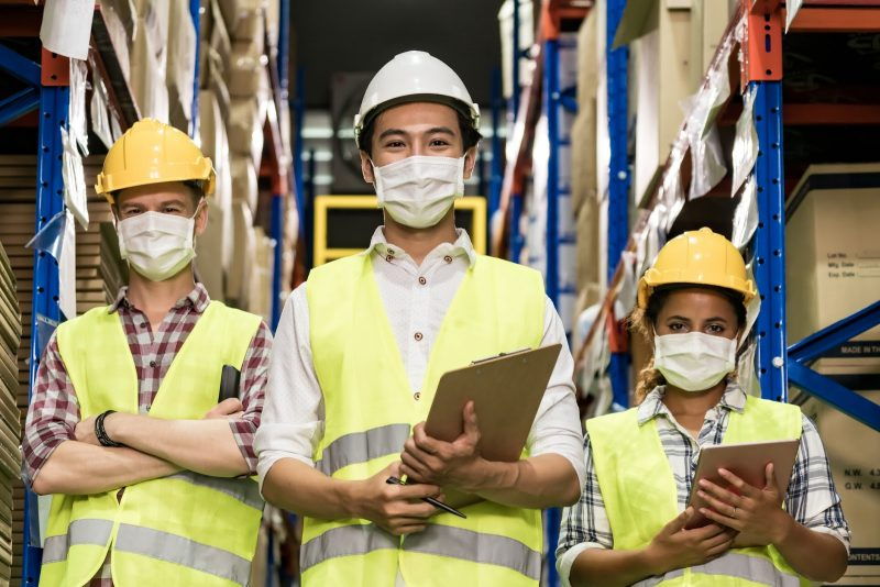 Three warehouse workers wearing masks with clipboards