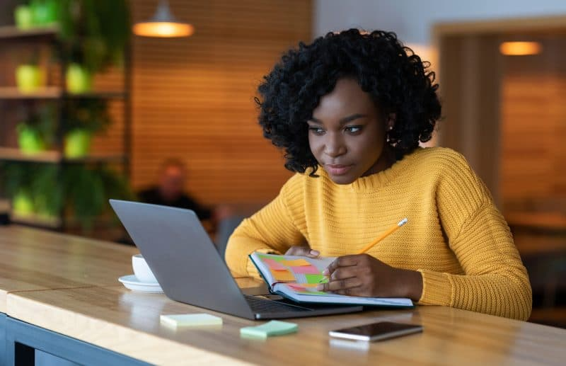 Woman in yellow sweater job searching on a laptop